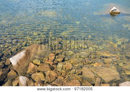Clear Water And Stones In Lake In Mountains.