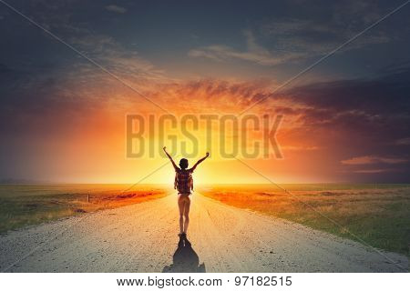 Rear view of girl with hands up facing sunrise