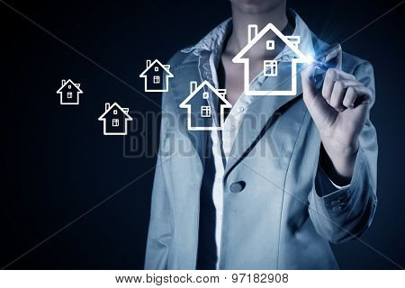 Businesswoman drawing house with pen on screen