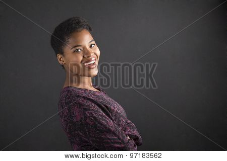 South African Or African American Woman Teacher Or Student With Arms Folded On Chalk Black Board Bac