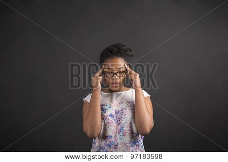 African Woman With Fingers On Temples Thinking On Blackboard Background