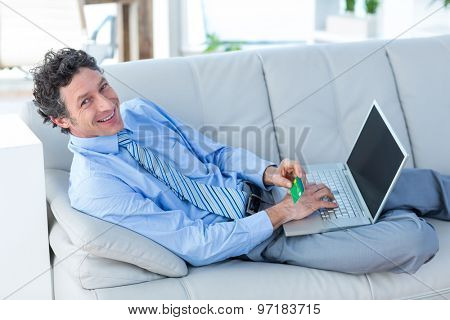Happy businessman doing online shopping on couch in living room