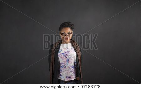 African Woman With Arms Behind Back On Blackboard Background