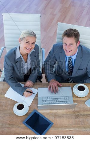 Smiling business people using laptop in the office