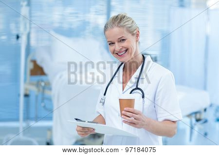 Beautiful smiling doctor holding clipboard and goblet in hospital room