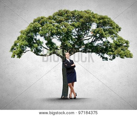 Businesswoman leaning on green tree with her back