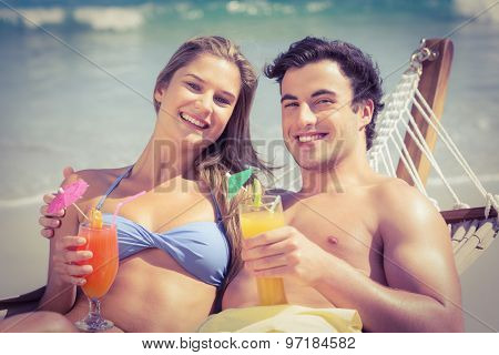 Cute couple in the hammock drinking a cocktail on the beach
