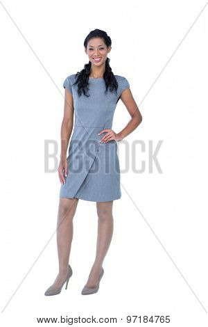 Happy pretty businesswoman looking at camera with hand on hip on white background