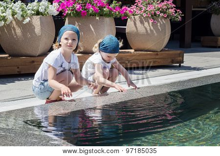 Funny Little Girls (sisters) Are Playing Near The Pool.