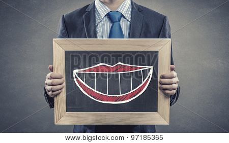 Close up of businessman holding wooden frame with smile