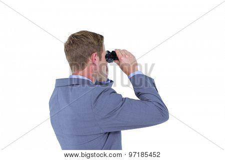 Businessman using binoculars against a white background