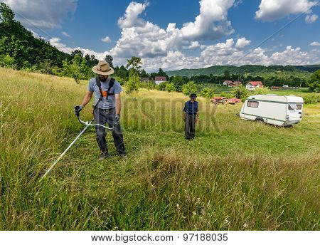 Young Farmer Mowing The Lawn