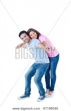 Happy man giving his girlfriend piggy back on white background