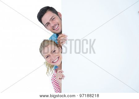 Smiling young couple hiding behind a blank sign on whit background