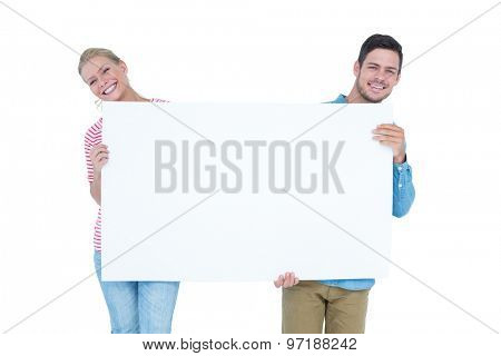 Smiling young couple holding a blank sign on white background