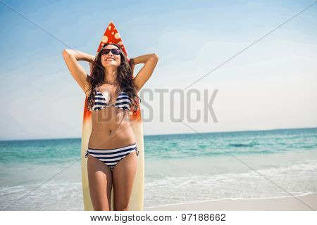 Pretty brunette with a surfboard on a sunny day at the beach