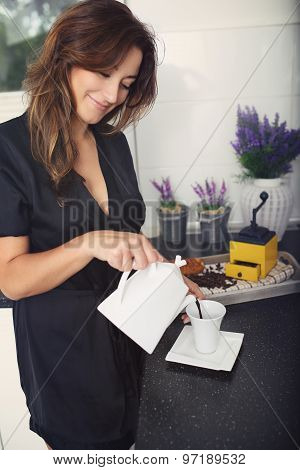 Cheerful And Smiling Woman Pours Coffee