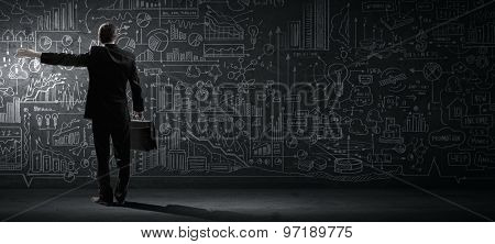Rear view of businessman looking at chalk business sketches on wall