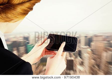 Businesswoman holding smartphone showing screen against new york