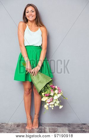 Full length portrait of a happy girl holding bouquet with flowers on gray background
