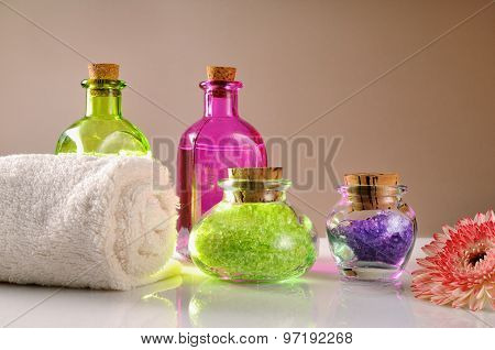 Oils And Bath Salts On White Glass Table