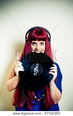 Young Pretty Woman With Headphones Biting Vinyl Record
