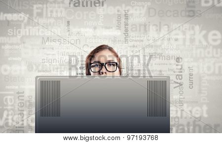 Young woman looking out above laptop monitor