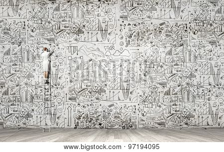Back view of businesswoman standing on ladder and drawing sketch on wall