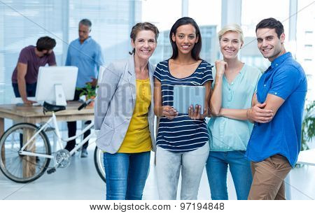 Businesswoman holding a tablet and looking at the camera in the office
