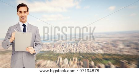 Happy businessman holding a clipboard against new york