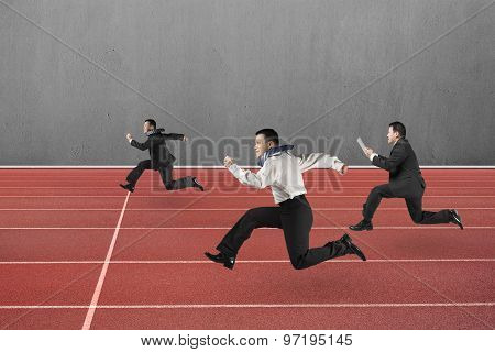 Three Businessmen Running On Red Track