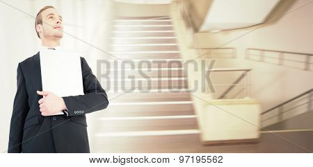 Businessman looking up holding laptop against empty stair way