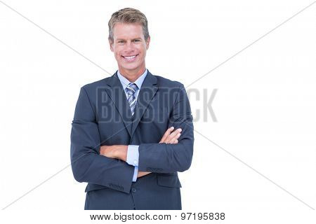 Smiling businessman with arms crossed against a white background