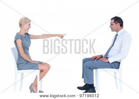 businesswoman pointing at businessman against a white wall