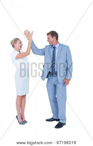 businessman and businesswoman greeting each other against white wall