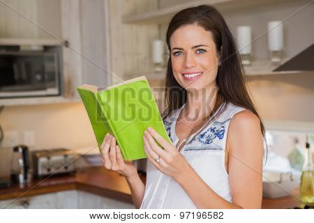 Smiling pregnancy reading a book on kitchen