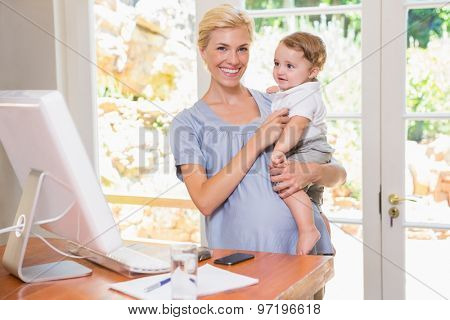 Blonde woman with his son using computer in the office