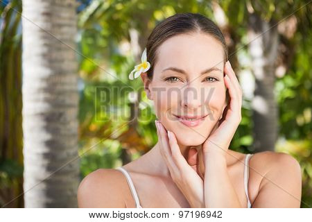 Beautiful natural brunette looking at camera on green background