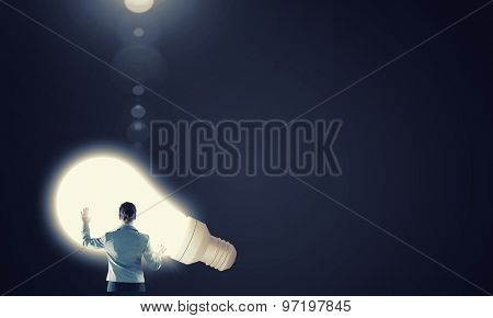 Back view of businesswoman and big glowing light bulb