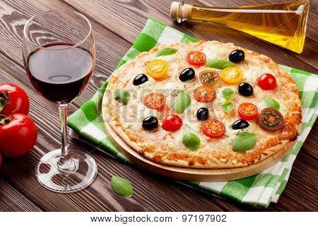 Italian pizza with cheese, tomatoes, olives, basil and red wine on wooden table