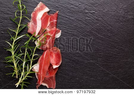 Prosciutto with rosemary on stone table. Top view with copy space