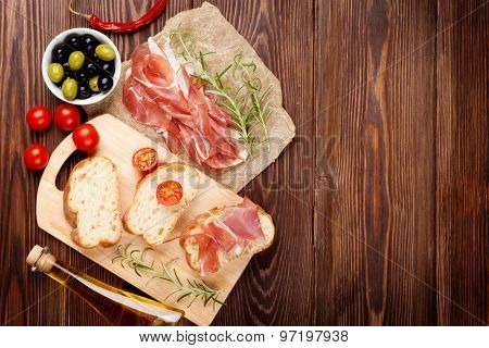 Bruschetta ingredients - prosciutto, olives, tomatoes. Top view on wooden table