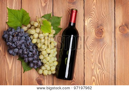 Red wine bottle and bunch of grapes on wooden table background