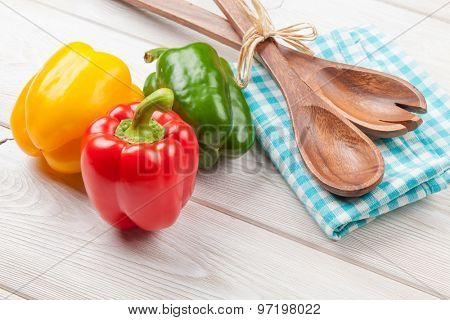Colorful bell peppers and kitchen utensil on white wooden table