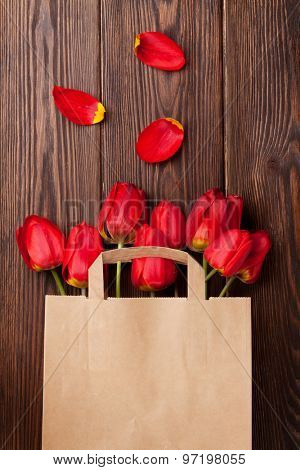Red tulips bouquet in paper bag over wooden table background with copy space