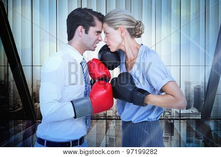 Business people wearing and boxing red gloves against window overlooking citty