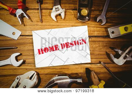 The word home design and digital tablet displaying blueprint against white card
