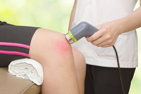 foto of knee  - Physical therapist using ultrasound probe on woman patient  - JPG