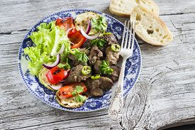 image of liver fry  - fried chicken livers grilled vegetables and a fresh green salad on the blue plate on a light wooden background - JPG