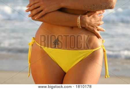 Mid Drift Woman In A Yellow Bikini And Tattoo